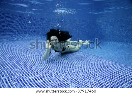 Underwater picture of a woman smiling and signing with hands. - stock photo