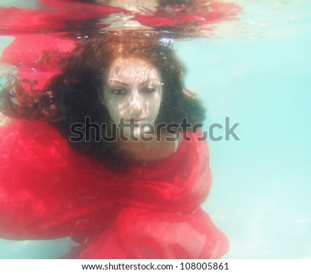 underwater portrait of young beautiful woman in red dress - stock photo