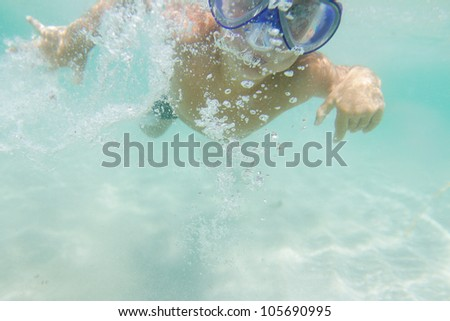underwater portrait of young boy diving with scuba mask - stock photo