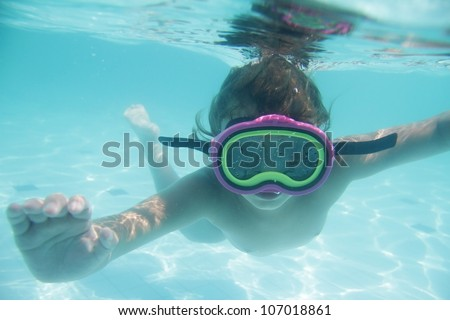 underwater portrait of young child diving in mask - stock photo