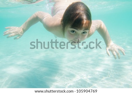 underwater portrait of young happy girl diving - stock photo