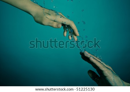 Underwater rescue concept. Female hand helping drowning male that going to dark sea floor. - stock photo