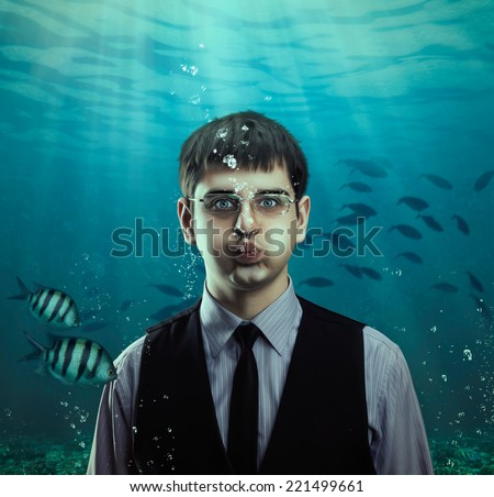 Underwater scene of a businessman with fishes - stock photo