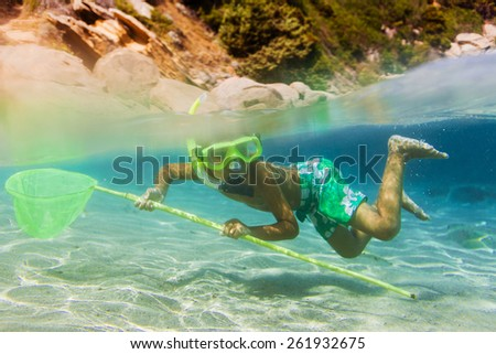 Underwater shoot of a cute boy snorkeling with scoop-net in a tropical sea - stock photo