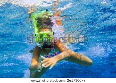 Underwater shoot of a cute girl snorkeling in a tropical sea - stock photo