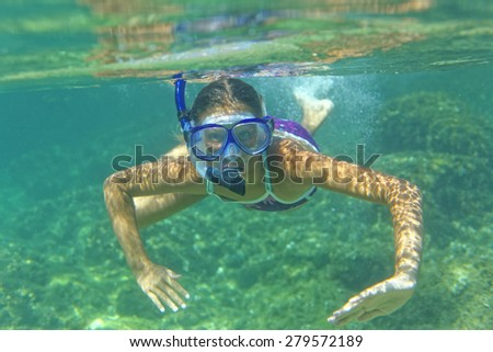 Underwater shoot of a cute girl snorkeling in a tropical sea