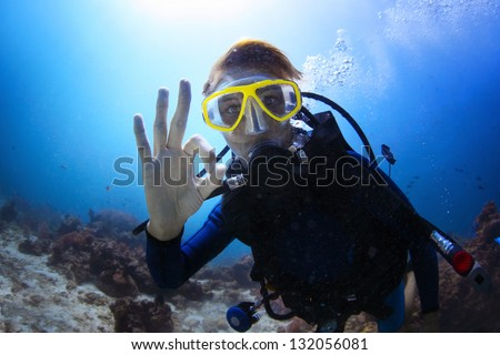 Underwater shoot of a woman diving with scuba and showing ok signal - stock photo