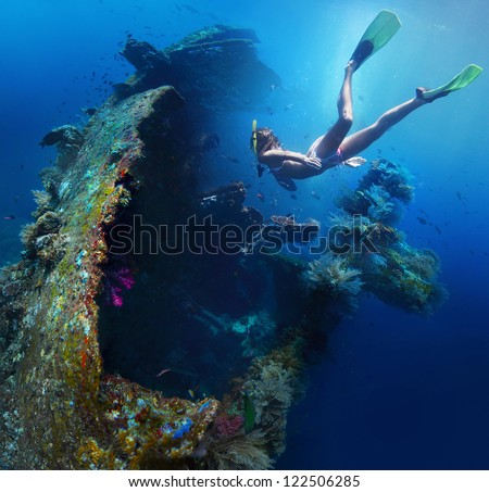 Underwater shoot of a woman exploring USAT Liberty wreck on a breath hold. Tulamben, Bali island, Indonesia - stock photo