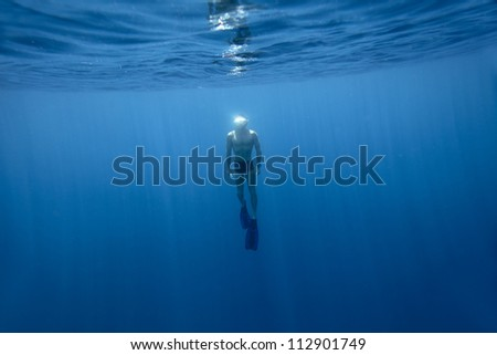 Underwater shoot of a young athlete finning from a depth to surface on a breath hold - stock photo