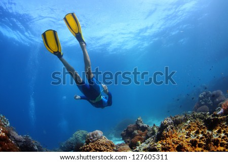 Underwater shoot of a young lady snorkeling and diving on a breath hold over vivid coral reef of tropical island - stock photo