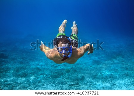 Underwater shoot of a young man snorkeling in a tropical sea. vacation concept - stock photo