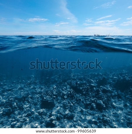 Underwater shoot of  coral reef combined with sea surface with waves and blue sky - stock photo