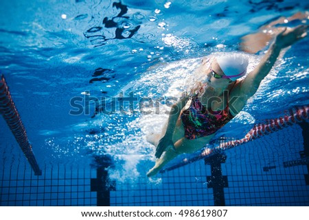 High Quality Underwater Shot Of Fit Swimmer Training In The Pool. Female Swimmer Inside  Swimming Pool.