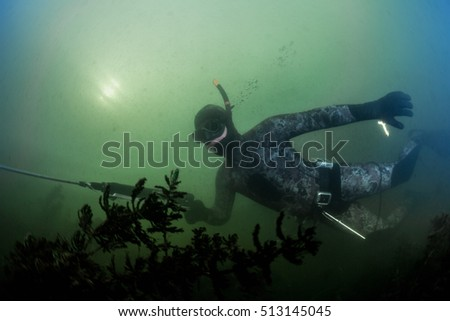 Underwater shot of the hunter with speargun in a lake