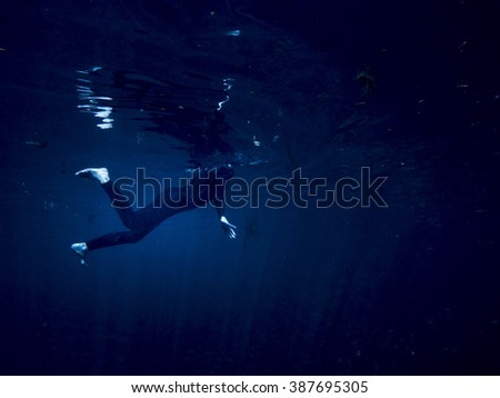 Underwater shot of woman swimming alone in the dark, concept shot