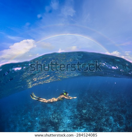 Underwater Sport Postcard. A female freediver with fins snorkeling under water surface in ocean. A rainbow appears on cloudy sky over beautiful seascape - stock photo