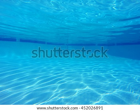 Underwater sunlight patterns in clean suburban swimming pool.   - stock photo