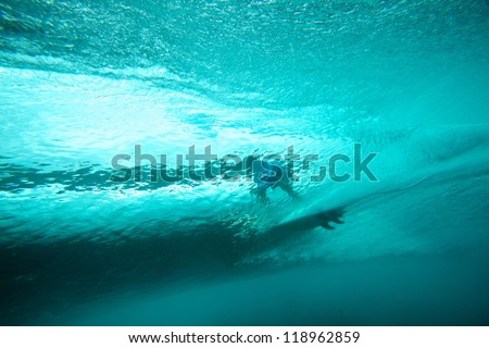 Underwater view of surfer and crystal clear wave - stock photo