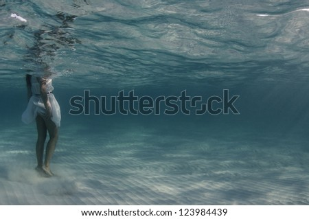 Underwater view of woman in white dress stands in shallow ocean water. - stock photo