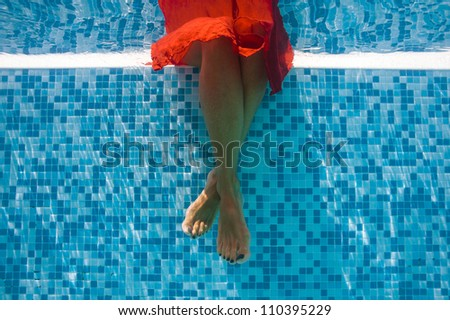 Underwater woman feet with red dress in swimming pool.