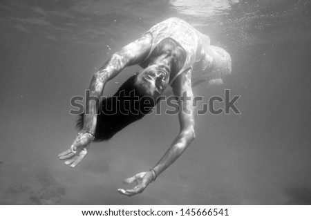 Underwater woman portrait with white dress into the sea. Black and white image.