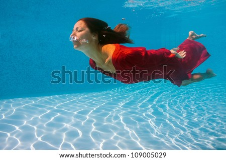 Underwater woman with red dress in swimming pool.