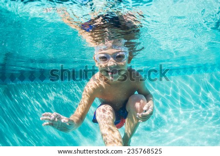 Underwater Young Boy Fun in the Swimming Pool with Goggles. Summer Vacation Fun. - stock photo
