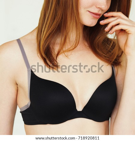 Underwear concept. Young smiling sexy woman with red hair in lingerie posing on white background. Hand near face. Natural style. Close up. Studio shot