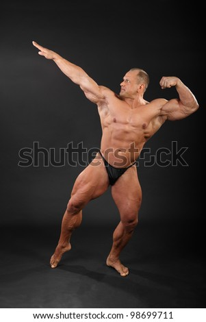Undressed tanned bodybuilder aiming for punch in black studio - stock photo