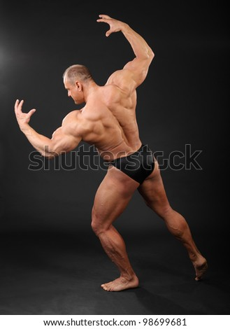 Undressed tanned bodybuilder shows muscles of arms and back in black studio - stock photo