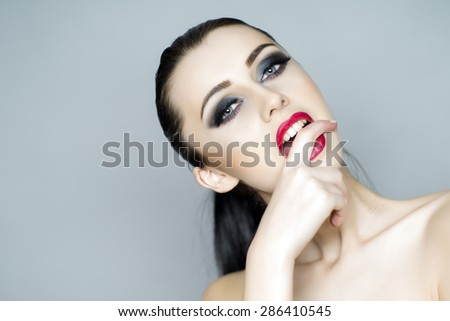 Undressed vamp brunette girl with bright makeup licking finger standing on light grey background copyspace, horizontal picture - stock photo