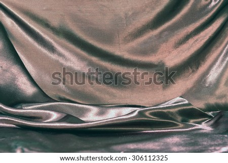 undulating folds of the fabric of black silk as festive background - stock photo