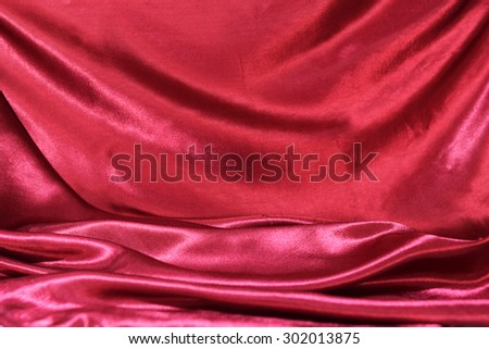 undulating folds of the fabric of dark red silk as festive background - stock photo