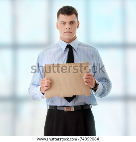Unemployed businessman with blank cardboard sign - stock photo