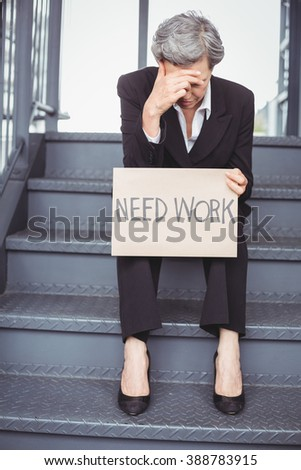 Unemployed businesswoman with need work placard sitting on staircase - stock photo