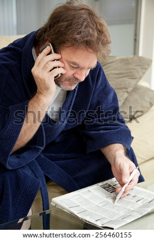 Unemployed man looking through the job listings and making phone calls.    - stock photo