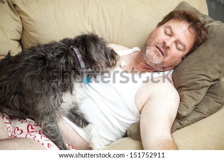 Unemployed man passed out on the couch in his underwear.  His dog is eating popcorn from his chest.   - stock photo