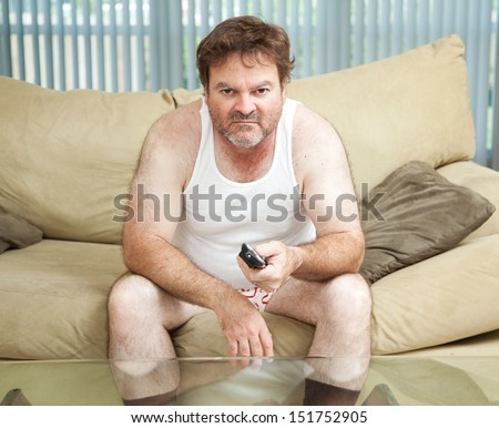 Unemployed man sitting home watching TV, bored and discouraged.   - stock photo