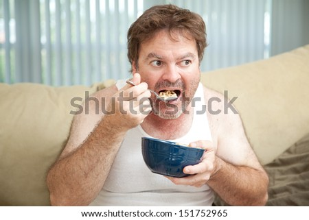 Unemployed man sitting on the couch eating cereal as he watches television.   - stock photo