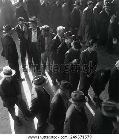 Unemployed men wait in line to file Social Security benefit claims. In January 1938, new Social Security programs made unemployment compensation available. California, by Dorothea Lange. - stock photo