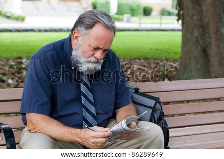 Unemployed middle aged man looks at advertisements for jobs in a newspaper while sitting on a park bench. - stock photo