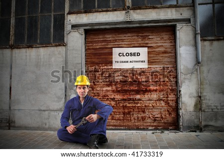 unemployed worker in front of closed workshop - stock photo