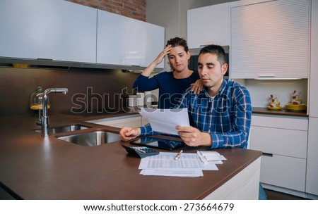 Unemployed young couple with many debts reviewing their bank accounts. Financial family problems concept. - stock photo