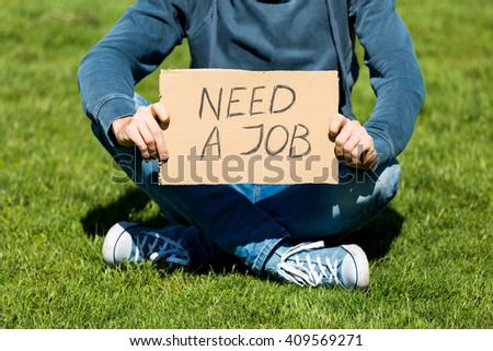 Unemployed young man with cardboard - stock photo