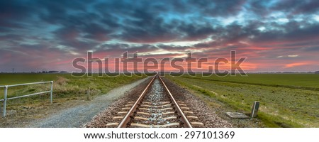 Unending railroad travelling to the horizon under a blue and red sky as a concept for heaven and freedom. - stock photo