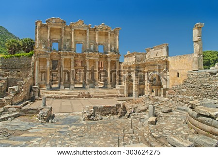 UNESCO heritage site Celsus library facade in Ephesus on sunny day with two palm trees, Turkey - stock photo