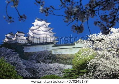 UNESCO world heritage site: Himeji castle and spring cherry blossoms at blue dusk, in Hyogo, Japan ~ A majestic Japanese castle surrounded by romantic sakura blossoms under moody evening sky - stock photo