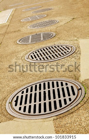 Uneven Line up of Sewer Drains on a sidewalk