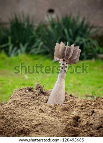 Unexploded mortar shell stuck in the ground. - stock photo