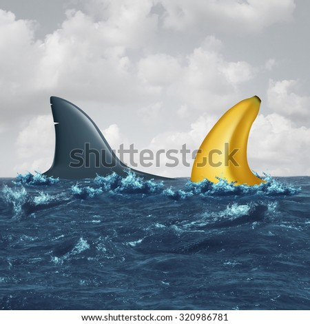 Unfair negotiation business concept and out of your league symbol as a shark fin facing off with a similar shaped banana as a metaphor for lack of skills and vulnerable negotiating icon. - stock photo